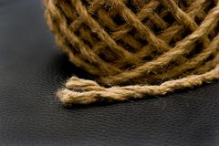 Frayed Rope On Leather Background. Ball of rope with stray frayed end extended.  Isolated on black leather background Stock Images