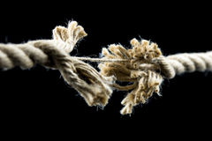 Frayed rope about to break. Closeup of frayed rope about to break. Isolated over black background stock photography