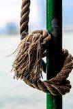 A Frayed Rope. A vertical photograph of a frayed rope tied to a pole on a boat stock photo