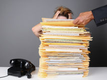 Frazzled Office Worker. A frazzled female office worker grabs her head in frustration as her boss piles more work on her desk. Horizontal format over a gray Stock Photo