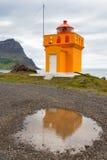 Färben Sie sich mit orange Leuchtturm, Reflexion in der Pfütze, Island gelb Stockfoto