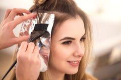 Färbendes Haar des Berufsfriseurs ihres Kunden Stockfoto