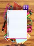 Förbigå den fodrade anteckningsboken med den bakomliggande ramen för skolatillförsel på trä Royaltyfri Bild