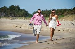 Förbunden running på strand Arkivfoton