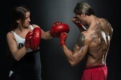 Färdig kvinna och hennes instruktör Boxing Indoors Royaltyfri Fotografi