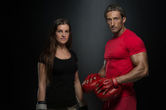 Färdig kvinna och hennes instruktör Boxing Indoors Royaltyfri Bild