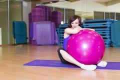 Färdig kvinna som gör övningar med en boll på ett mattt i en idrottshall Arkivbild