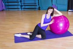 Färdig kvinna som gör övningar med en boll på ett mattt i en idrottshall Arkivfoto