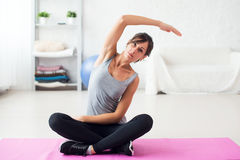 Färdig kvinna som tillbaka sträcker hennes övning för rygg Royaltyfri Bild