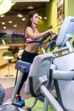 Färdig kvinna som övar på genomköraren för instruktör för fotgängare för konditionidrottshallaerobics den ellipsformiga Arkivfoto