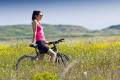 Färdig kvinnaridningmountainbike Arkivfoto