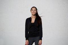 Färdig och sund kvinna som tycker om solsken, medan stå utomhus på vit väggbakgrund Fotografering för Bildbyråer