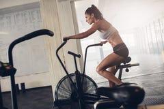 Färdig ung kvinna som använder motionscykelen på idrottshallen Royaltyfria Bilder