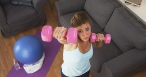 Färdiga lyftande vikter för ung kvinna hemma Fotografering för Bildbyråer