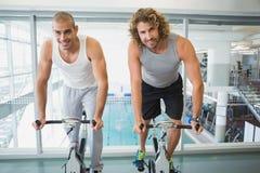 Färdiga män som arbetar på motionscykeler på idrottshallen Royaltyfria Foton