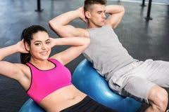 Färdiga par som gör buk- knastranden på konditionboll Arkivbild