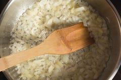 Freír la cebolla en una cacerola Foto de archivo libre de regalías