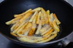 Freír las patatas en una cacerola Foto de archivo libre de regalías