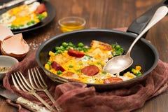 Freír los huevos con las salchichas ahumadas y las verduras imagen de archivo