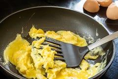 Freír los huevos revueltos en un negro de la cacerola Imagen de archivo libre de regalías