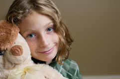 Freackle faced blue eyed girl. Adorable blue eyed girl with freckles looking at the camera and snuggling her toy Royalty Free Stock Photo