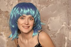 Freak concept. Lady on smiling face posing in blue wig, concrete wall background. Woman with blue hair looks unordinary. And extraordinary. Lady freak with royalty free stock photography