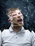 Freak man with rubber on his face. Isolated over gray background Stock Photo