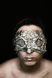 Freak in mask. Freak in foil mask and reticulated facet eye covers on black Royalty Free Stock Photo