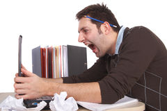 Freak out. A young stressed out man is screaming at his laptop in anger. Isolated over white Royalty Free Stock Images