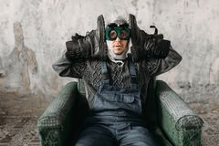 Freak in swimming goggles wearing shoes on hands. Funny freak man in swimming goggles wearing shoes on his hands, grunge room interior. Nerd in abandoned house royalty free stock image