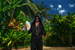Freak in tropic garden. Freak in black clothe and glasses holding fan Royalty Free Stock Photo