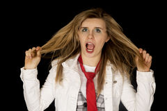 Freaking out young female pulling hair black background. Freaking out female pulling hair black background Royalty Free Stock Photo