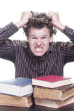 Freaking out. Young stressed male Caucasian student freaks out pulling hair with pile of academic books on desk on white background Royalty Free Stock Photography