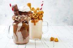 Freakshake fou de caramel et de chocolat, milkshakes avec des gaufres de brezel, maïs éclaté, guimauve, crème glacée et crème fou images stock