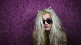 Freaky blonde girl in sunglasses and kitty ears. On purple background. Unusual young woman moves head and looking in camera stock video footage