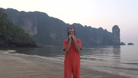 Freaky Caucasian Man in Traditional Thai Womens Hat Playing on his Harp at the Morning Twilight on the Coastline of. Beautiful Tropical Rocky Cliff Lagoon in stock video