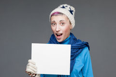 Freaky girl in winter clothing holding sign Stock Images