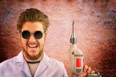 Freaky mad doctor with drill. Freaky mad doctor in white coat and dark sunglasses with drill in hand on creepy red background. Halloween concept royalty free stock image