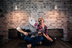 Freaky man in comical mask and causal clothes playing music on guitar royalty free stock photography