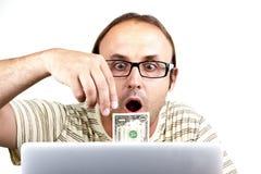 Freaky-man-med-bärbar dator-och-pengar Arkivbild