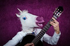 Freaky young man in comical mask playing the guitar on the purple background. Portrait of unusual guy in shirt and tie with musical instrument. Musical Stock Image