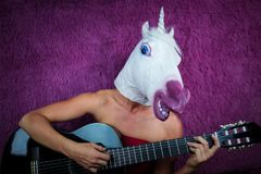 Freaky young woman in comical mask playing the guitar on the purple background royalty free stock photos