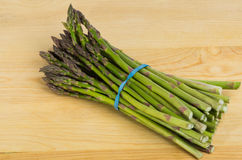 Freash asparagus on wooden cutting board Stock Photos