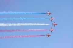 Frecce di colore rosso di volo di formazione Fotografia Stock
