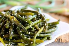 Frecce fritte dell'aglio con la miscela ed i semi di sesamo delle spezie Frecce verdi saporite dell'aglio su un piatto bianco Immagini Stock Libere da Diritti