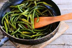 Frecce fritte dell'aglio in una padella e su una tavola di legno d'annata Alimento di verdure semplice e sano Immagine Stock