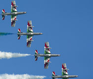 Frecce tricolori at an airshow. Four `Frecce tricolori` performing aerobatic maneuvers in the sky with colored smoke Stock Image