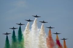 Frecce Tricolori flying in V formation and leaving Italian flag colored smoke trails. Stock Photo