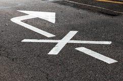 Freccia bianca attraversata, segnaletica stradale fotografia stock