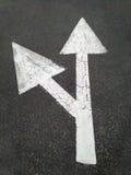 Freccia bianca della strada sull'asfalto Immagini Stock
